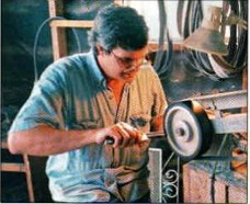Rocket Rob Davidson grinding a blade at the belt sander in his small machine shop in        Granite Shoals, Texas